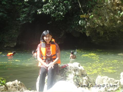 Bongkahan batu di tepi kolam di seberang mulut Goa Coban